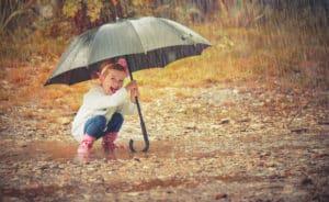 fröhliches Mädchen mit Regenschirm