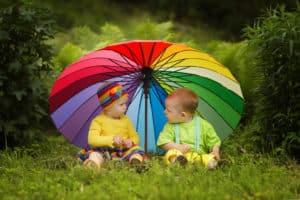 zwei kleine Kinder mit buntem Regenschirm