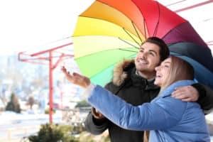 glückliches Paar mit buntem Regenschirm