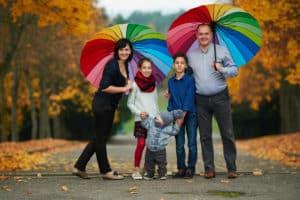 fröhliche Familie mit Regenschirmen